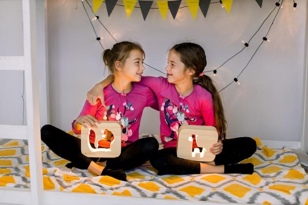 Glückliche kinder, zwei süße 10-jährige mädchenschwestern, im kinderzimmer auf einem etagenbett, sitzen in lotussitz, schauen sich an und halten hölzerne nachtlampen mit ausgeschnittenen bildern.