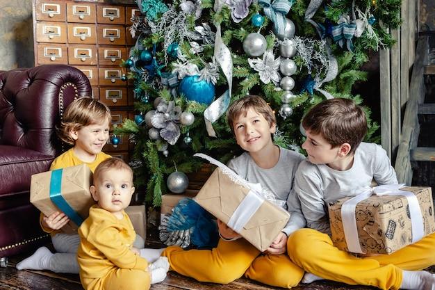 Glückliche kinderbrüder, die geschenke vor weihnachtsbaum öffnen
