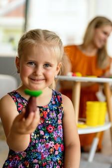 Glückliche kindergruppe, die spaß und spiel im kindergarten mit lehrer hat