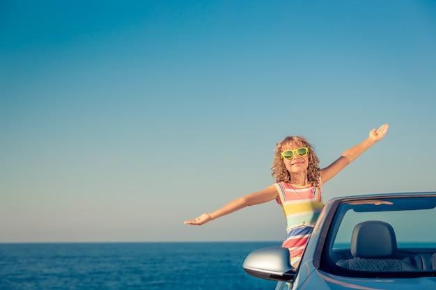 Glückliche kinderreisen mit dem auto kind, das spaß im blauen cabriolet sommerferienkonzept hat