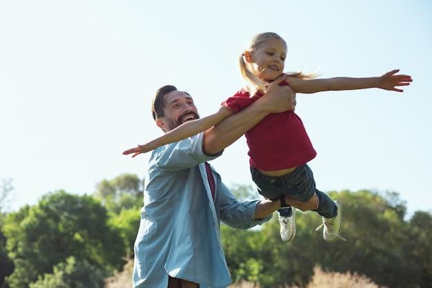 Glückliche kindheit. inspirierter bärtiger vater, der lächelt, während er spaß mit seiner kleinen tochter hat