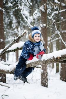 Glückliche kindheit - kleiner netter junge, der einen baum in einem schneebedeckten wald im winter klettert