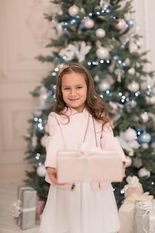 Glückliche kindheit, magische weihnachtsgeschichte. kleine prinzessin mit weihnachtsgeschenk zu weihnachten.