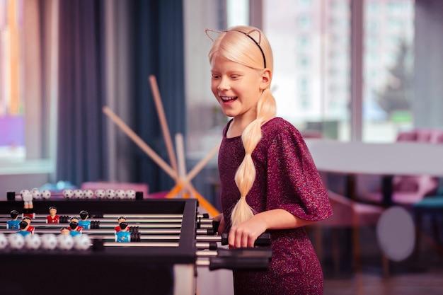 Glückliche kindheit. nettes kind mit blonden haaren, die stereotypen brechen und mit ihren freunden konkurrieren