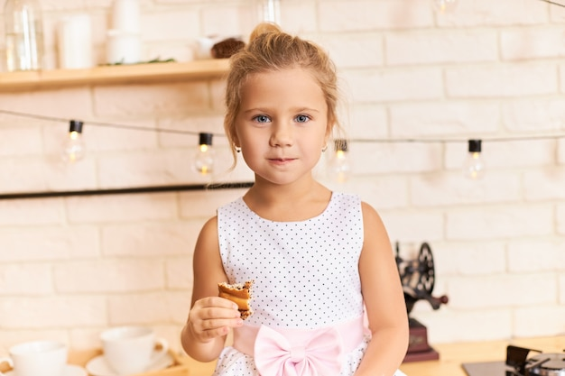 Glückliche kindheit, spaß und freude konzept. innenaufnahme des süßen entzückenden babymädchens, das schönes kleid trägt, das am esstisch im stilvollen kücheninnenraum sitzt, lacht, köstlichen keks oder kuchen kaut