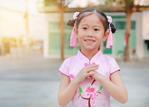Glückliche kleine asiatische mädchengruß-gestenfeier für chinesisches neujahr.
