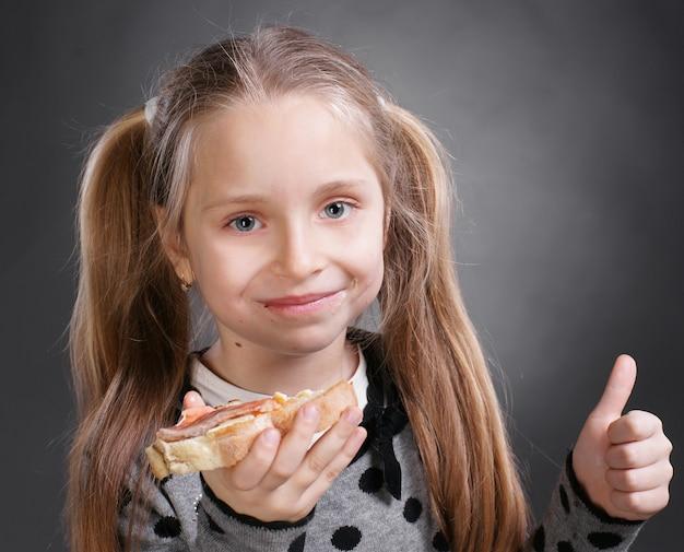 Glückliche kleine frau, die brot und butter mit fisch isst und ja-zeichen zeigt