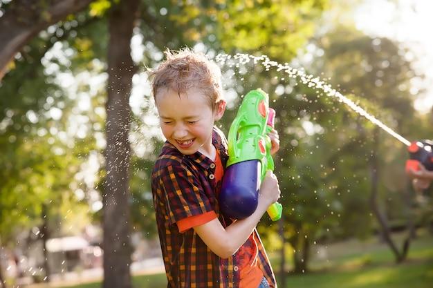 Glückliche kleine jungen, die mit wasserwerfern spielen