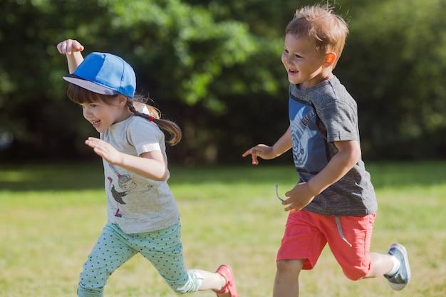 Glückliche kleine kinder, die aufholjagd spielen