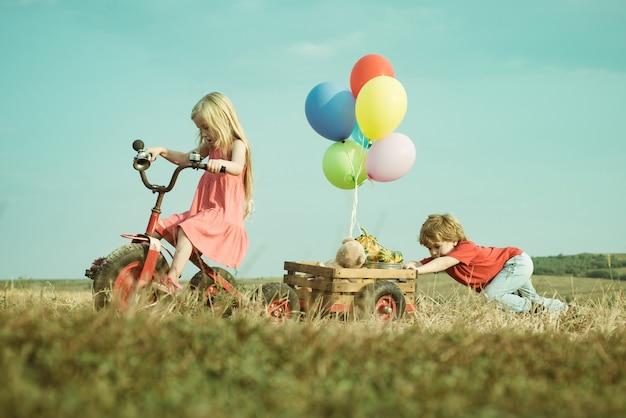 Glückliche kleine kinder, die enge freunde lächeln, während sie sich im freien amüsieren, kleine kinder haben spaß auf fr...