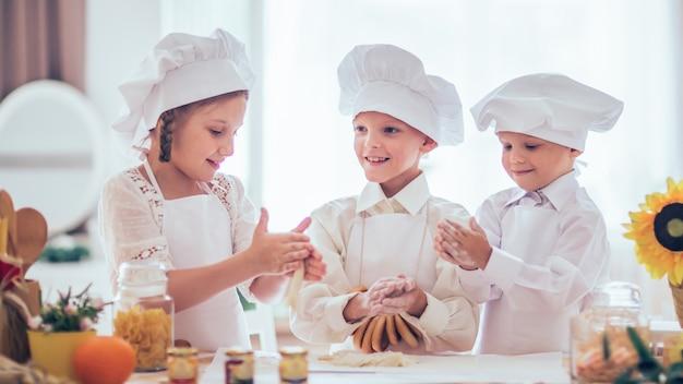Glückliche kleine kinder in form eines küchenchefs kochen ein köstliches frühstück in der küche