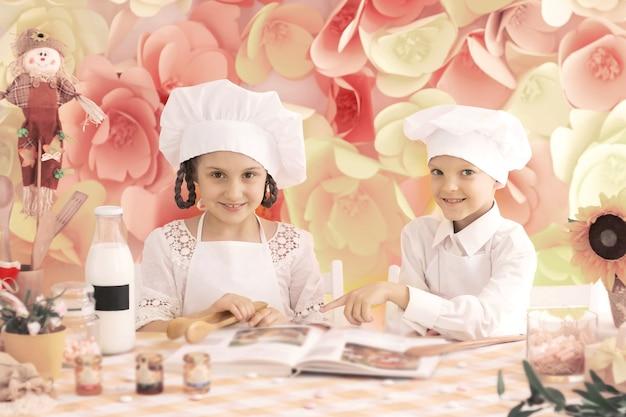 Glückliche kleine kinder in kochform, um köstliche gerichte in der küche zu kochen