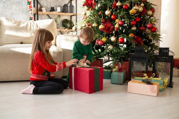 Glückliche kleine kinder mit weihnachtsgeschenkboxen.