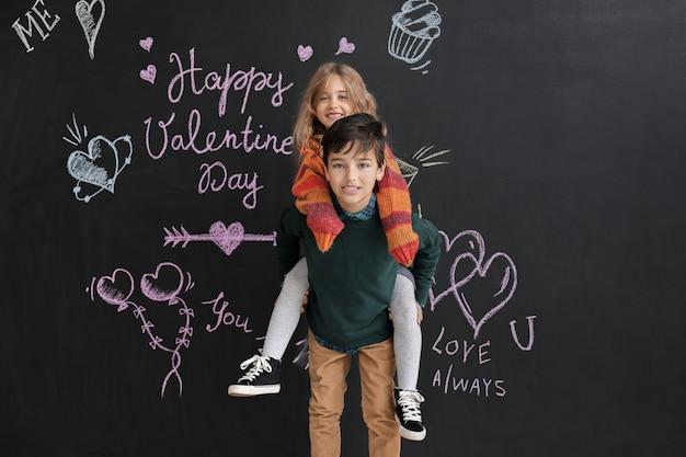 Glückliche kleine kinder nahe dunkler wand valentinstag feier valentine