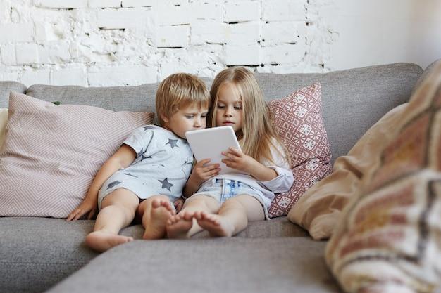 Glückliche kleine kinder sitzen im wohnzimmer