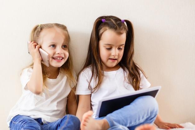 Glückliche kleine mädchen des technologie- und hauptkonzeptes mit tabletten-pc-computern