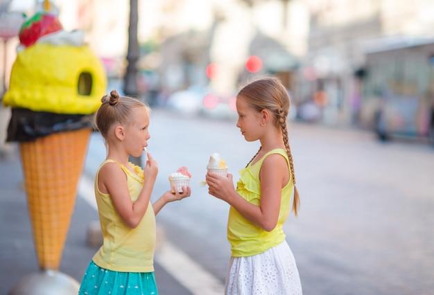 Glückliche kleine mädchen, die eiscreme-freiluftcafé essen. menschen, kinder, freunde und freundschaftskonzept