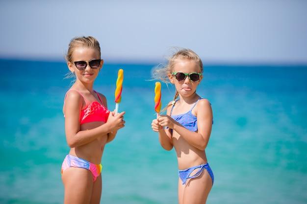 Glückliche kleine mädchen, die eiscreme während der strandferien essen. menschen, kinder, freunde und freundschaftskonzept