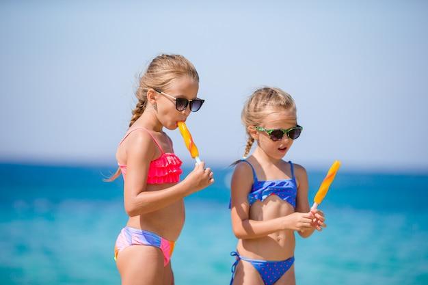 Glückliche kleine mädchen, die eiscreme während der strandferien essen