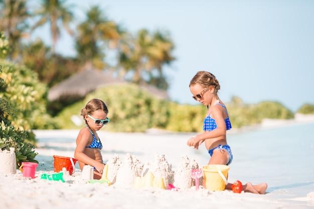 Glückliche kleine mädchen, die mit strandspielwaren während der tropischen ferien spielen