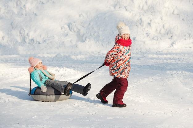 Glückliche kleine mädchen, die snowtubing rutschen