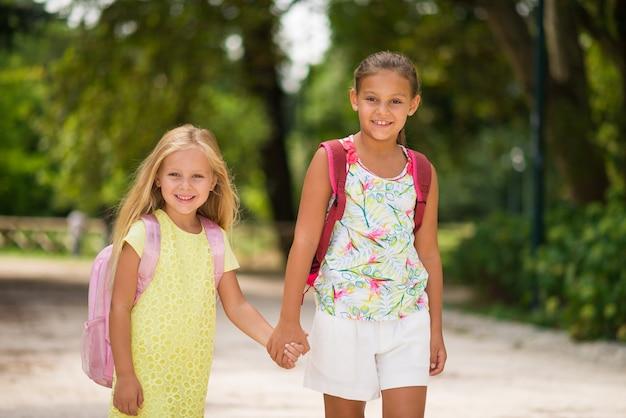 Glückliche kleine mädchen, die zusammen zur schule gehen