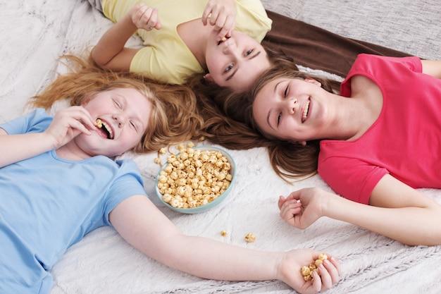 Glückliche kleine mädchen essen popcorn zu hause