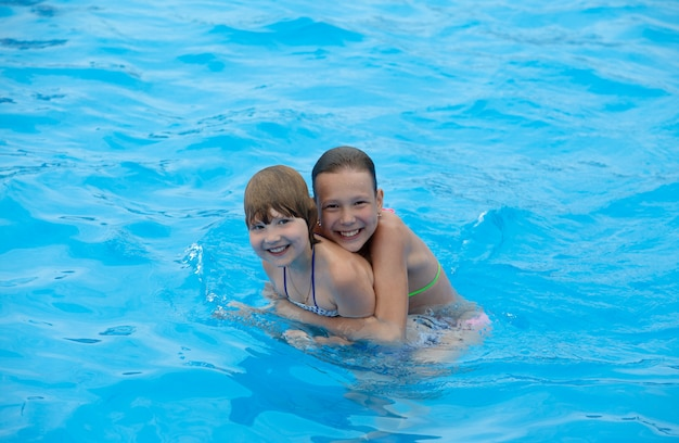 Glückliche kleine mädchen haben spaß beim schwimmen im pool