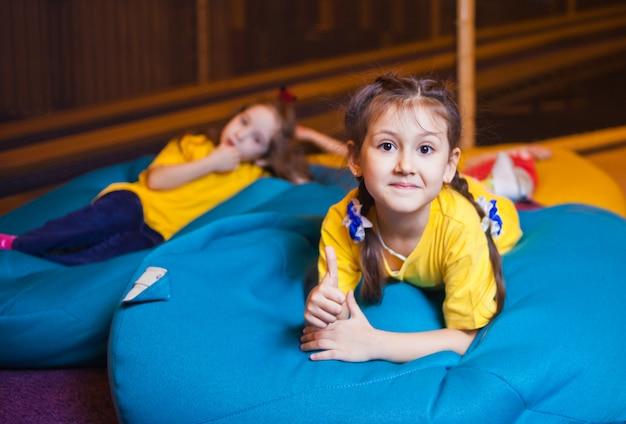 Glückliche kleine mädchen liegen auf der stuhltasche im kinderunterhaltungszentrum