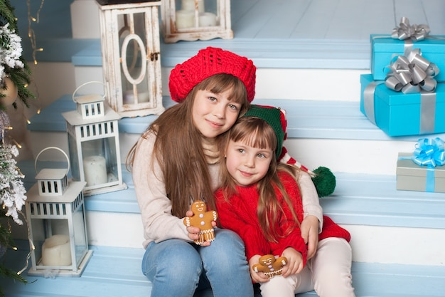 Glückliche kleine schwestern, die zu weihnachten auf veranda zu hause umarmen