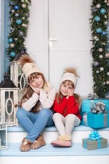 Glückliche kleine schwestern sitzen zu weihnachten auf der veranda zu hause