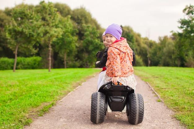 Glückliche kleine süße mädchen fahren draußen ein motorrad