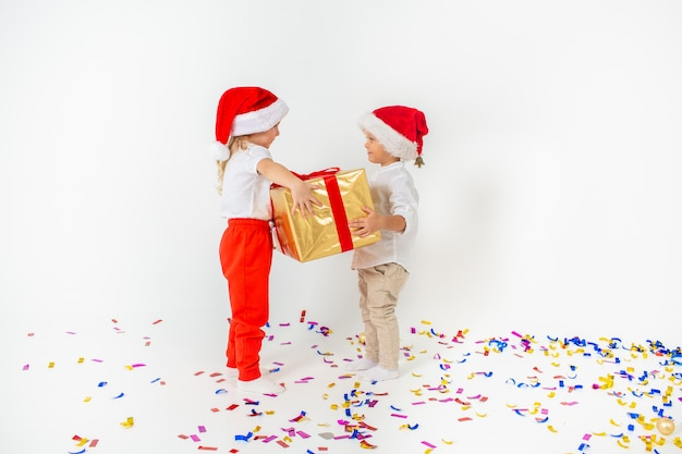 Glückliche kleinkinder in sankt-hut, der große geschenkbox hält. isoliert auf weißem hintergrund verkauf, feiertage, weihnachten, neues jahr, weihnachtskonzept.