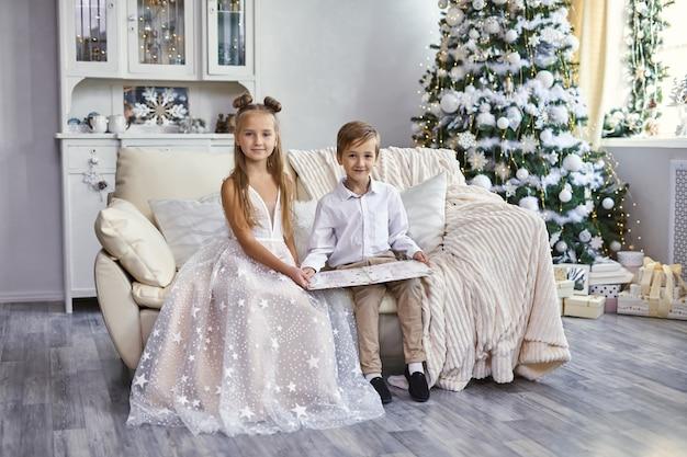 Glückliche klug gekleidete kleine kinder, die auf sofa sitzen