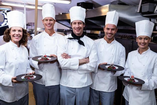 Glückliche köche präsentieren ihre dessertteller