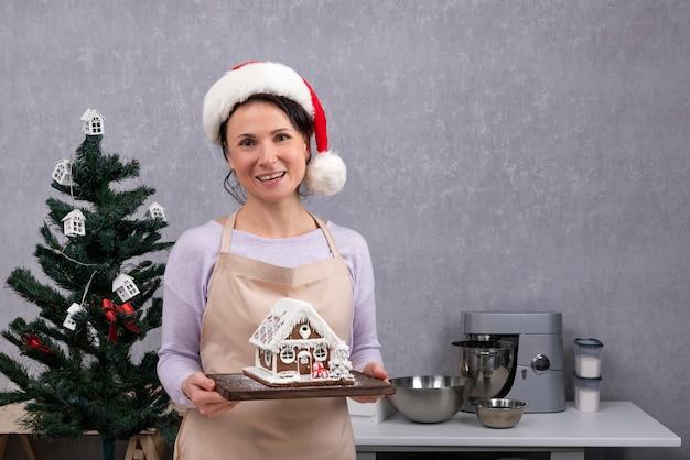 Glückliche köchin in der weihnachtsmütze hält lebkuchenhaus in ihren händen. weihnachtsdekorationen.
