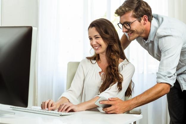 Glückliche kollegen, die computer im büro verwenden