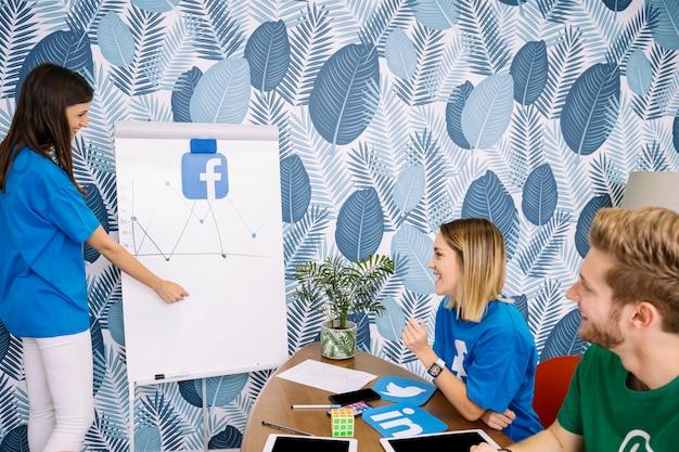Glückliche kollegen, die facebook-diagramm betrachten
