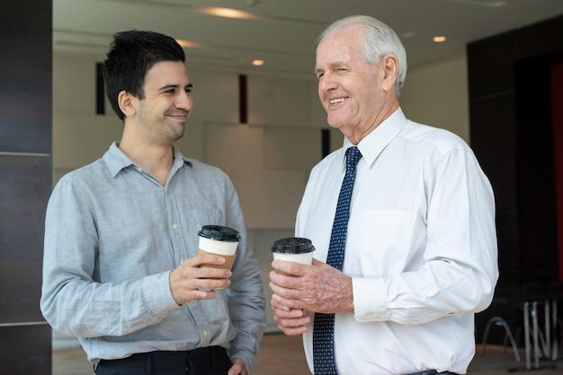 Glückliche kollegen mit kaffee zum mitnehmen