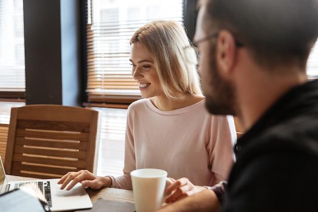 Glückliche kollegen sitzen im büro und arbeiten mit