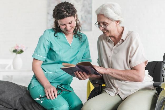 Glückliche krankenschwester, die buchgriff durch den älteren weiblichen patienten sitzt auf rollstuhl betrachtet