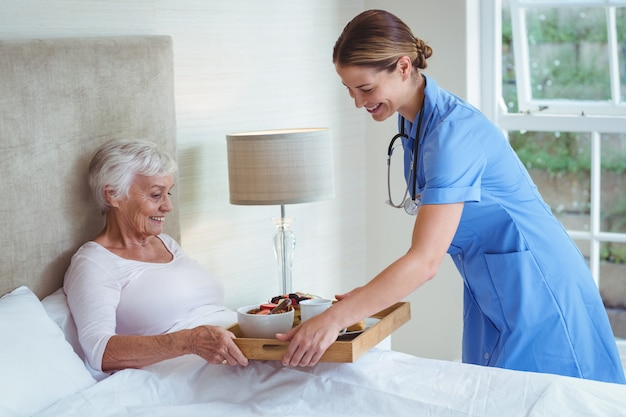 Glückliche krankenschwester, die der älteren frau lebensmittel gibt
