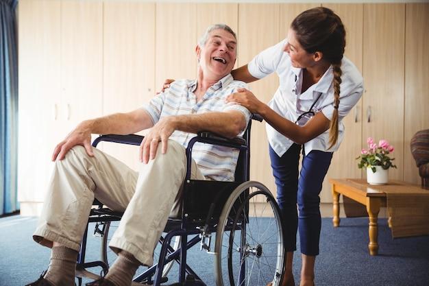 Glückliche krankenschwester, die zu seinem patienten lächelt