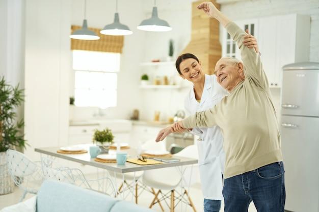 Glückliche krankenschwester und seniorin stehen im wohnzimmer