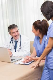 Glückliche krankenschwestern, die mit doktor plaudern