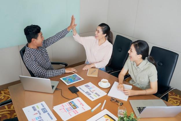 Glückliche kreative asiatische kollegen, die am schreibtisch im büro sitzen und high-five tun