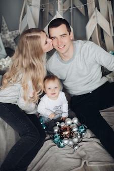 Glückliche küssende eltern und baby unter weihnachtsgeschenken