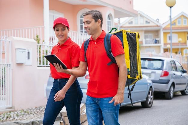 Glückliche kuriere liefern bestellung, arbeiten im expressdienst und tragen rote mütze und hemd. lieferbote, der gelben rucksack trägt und tablette hält. lieferservice und online-shopping-konzept