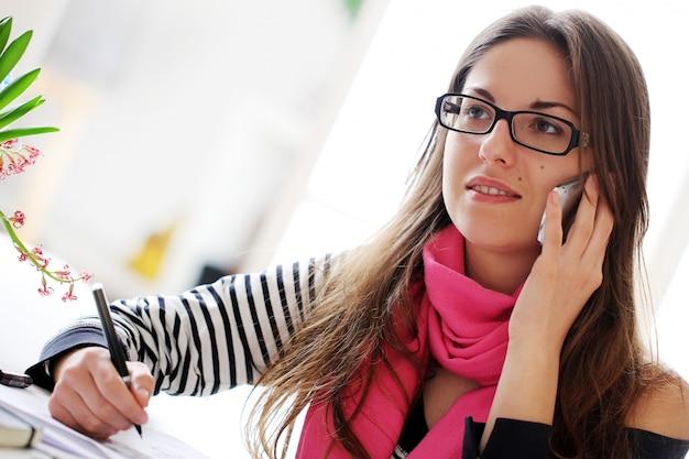 Glückliche kursteilnehmerfrau mit mobiltelefon