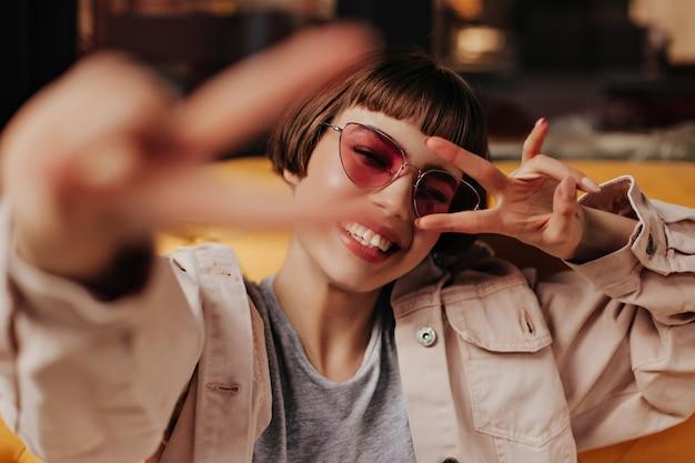 Glückliche kurzhaarige frau in leichter kleidung lächelt und sitzt auf der gelben couch im café